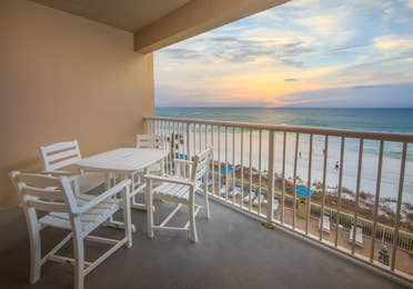 Furnished balcony with table and four chairs in a one-bedroom villa at Panama City Beach Resort