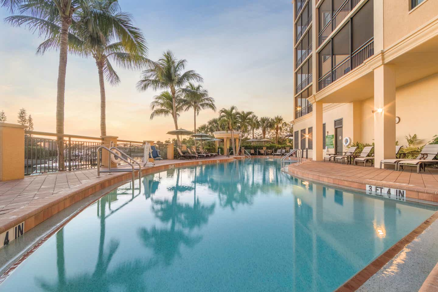 Outdoor pool surrounded by palm trees at Sunset Cove Resort