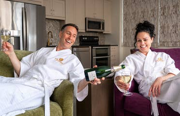 A man wearing a white robe on a green couch (left) holds a glass of champagne in his right hand while pouring the green bottle in this left hand for a woman (right) also wearing a white robe on a purple couch.