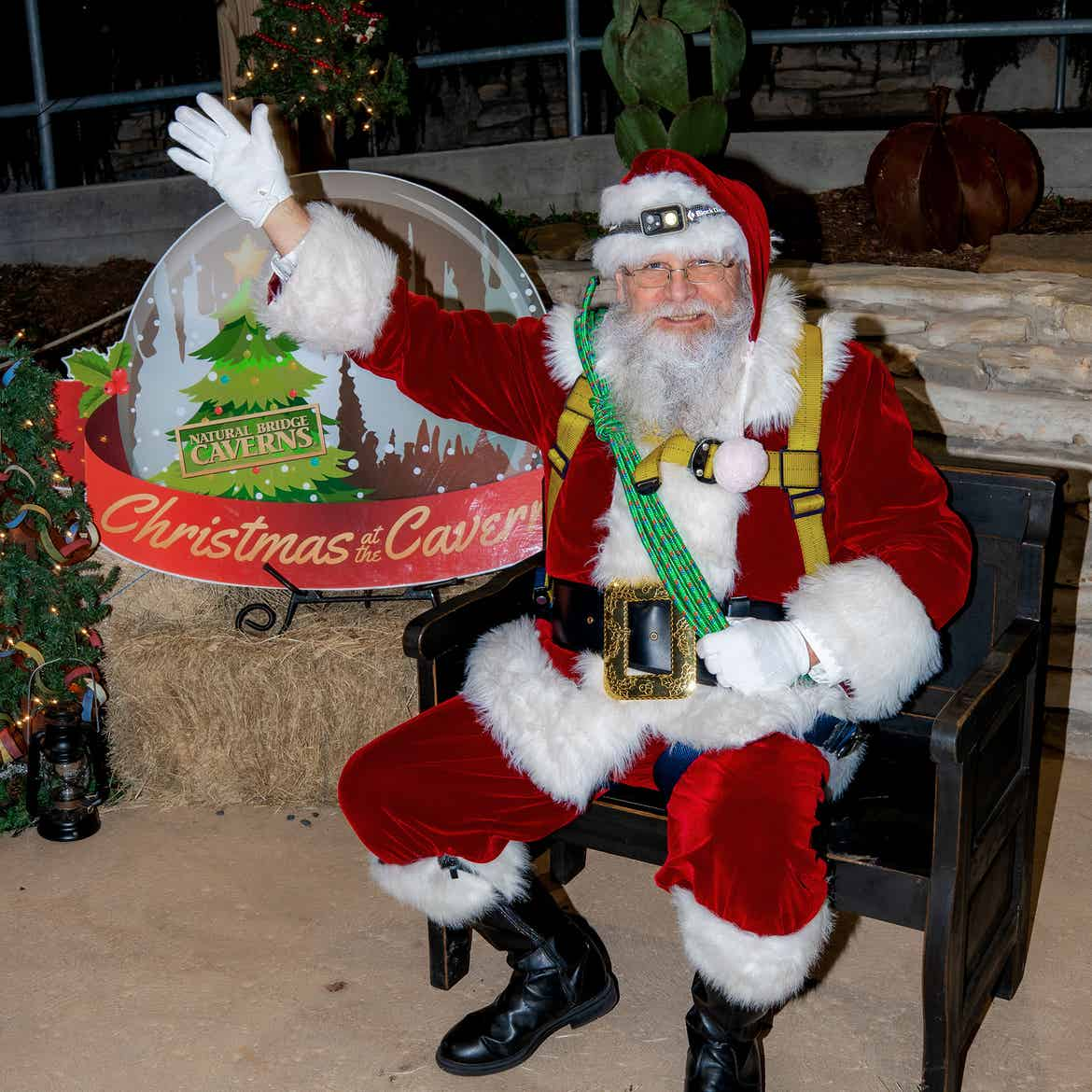 Santa 'Spelunker' Clause sits wearing his red suit, and climbing harness while waving to guests from a black bench in front of a snow globe that reads, 'Christmas & Caverns.'