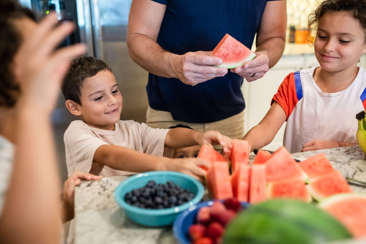 Brenda's husband, Isaiah, preps tasty fruits at the kitchen countertop with his sons watching.