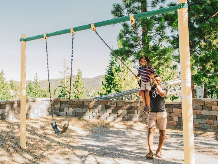 Father pushing child on swing at Tahoe Ridge Resort in Stateline, Nevada.