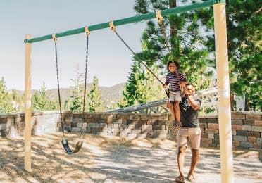 Father pushing child on swing at Tahoe Ridge Resort in Stateline, Nevada.