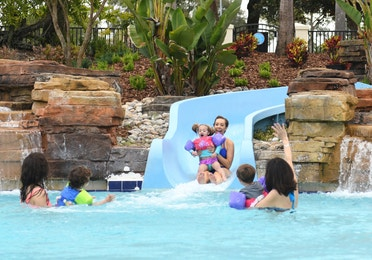 Mom and young girl sliding down water slide at Orange Lake Resort near Orlando, Florida