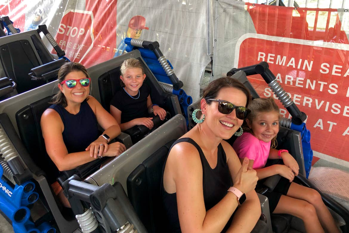 Two women (front) and two young girls (back) sit on a ride vehicle.