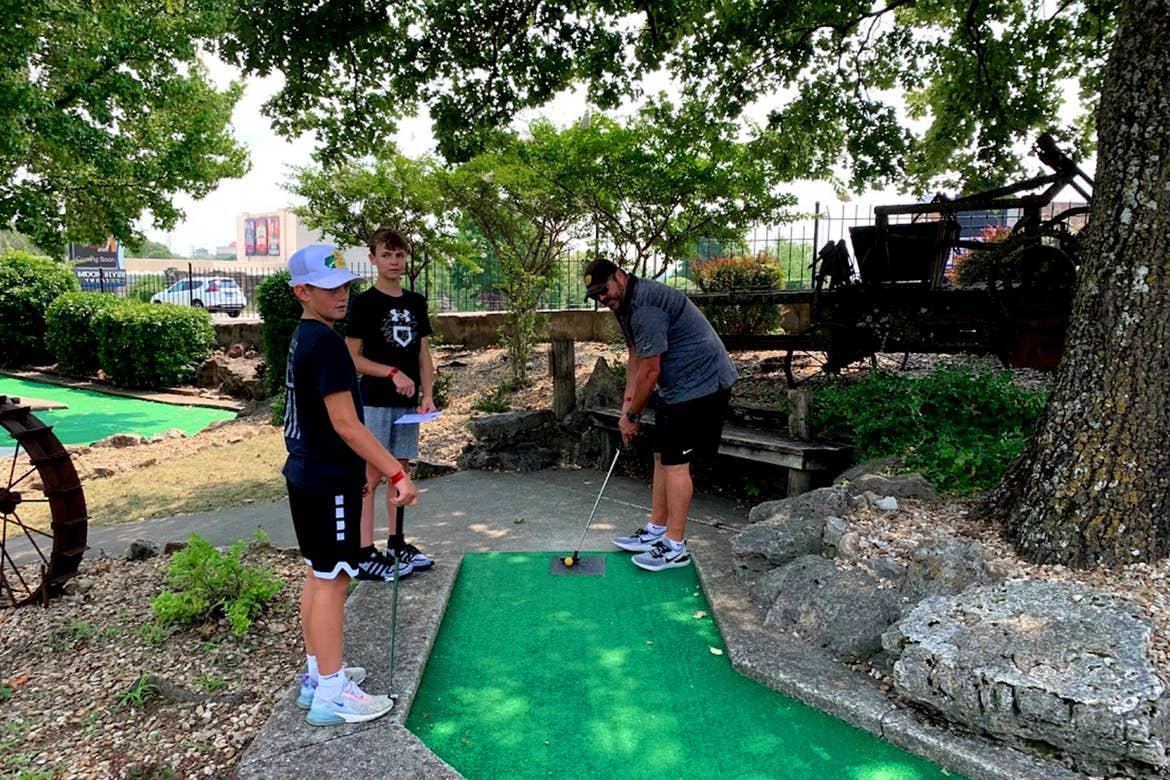 Two boys and a man play a round of mini golf on a course.