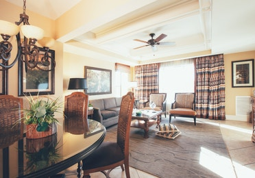 View of dining room table and living room with access to furnished balcony in a Signature villa in River Island at Orange Lake Resort near Orlando, Florida