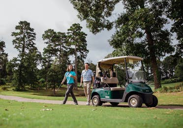 Couple standing next to golf cart on golf course at Eagle's Bluff Country Club near Villages Resort in Flint, Texas.