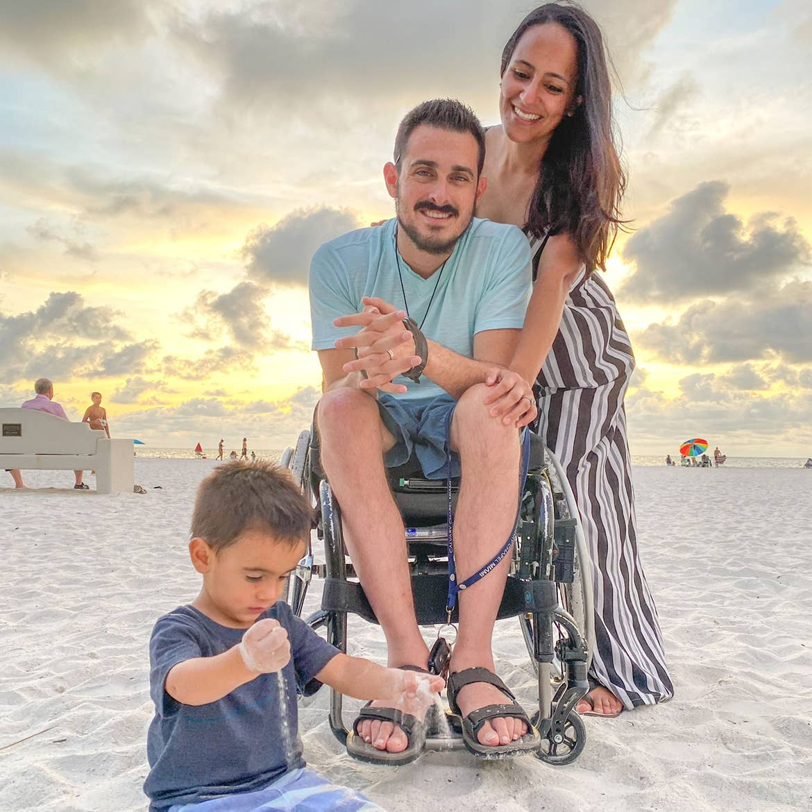 Author, Danny Pitaluga (middle), his wife, Val (right) and son, Joey (left), pose on a white sandy beach with a cloudy sunset behind them.