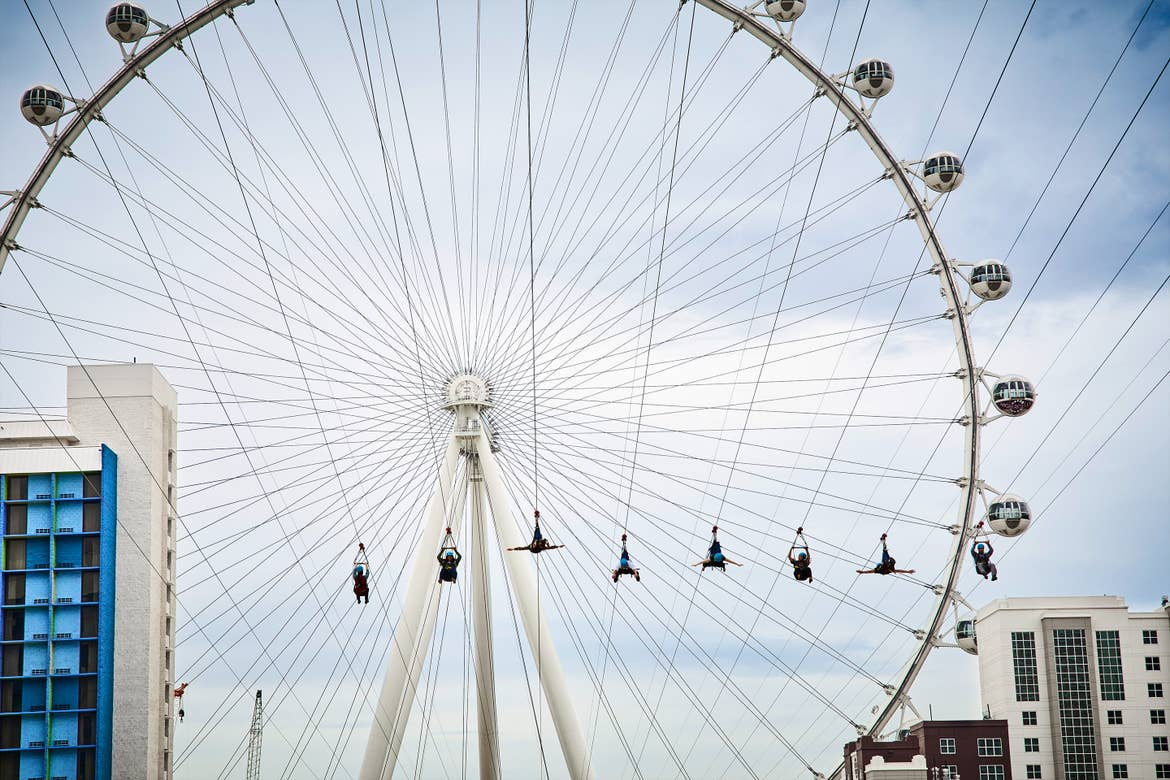 Several people are harnessed onto ziplines as they approach the 'High Roller' ferris wheel under a cloudy sky.