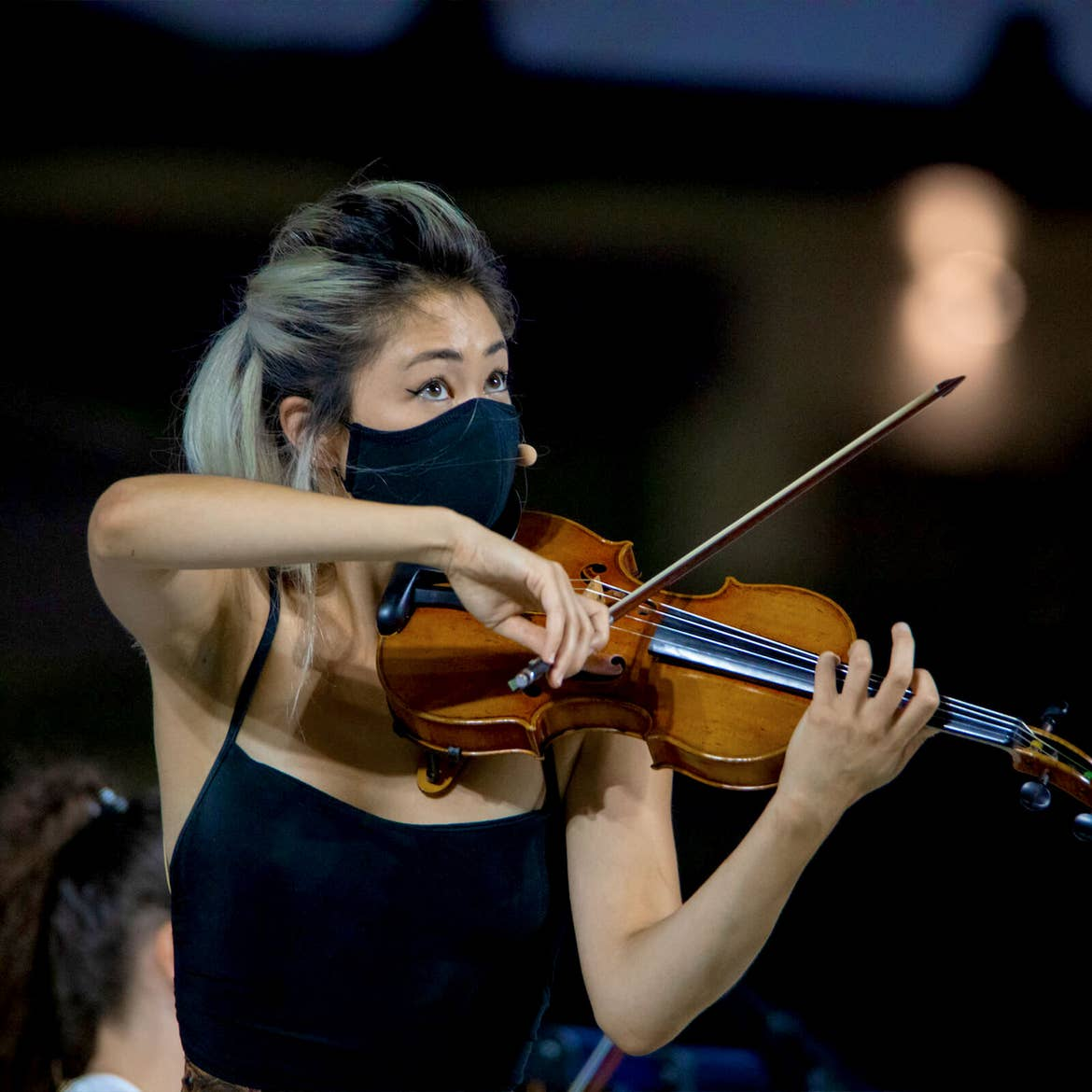 A violinist wears a black face mask while performing at Orlando Philharmonic at Exploria Stadium.