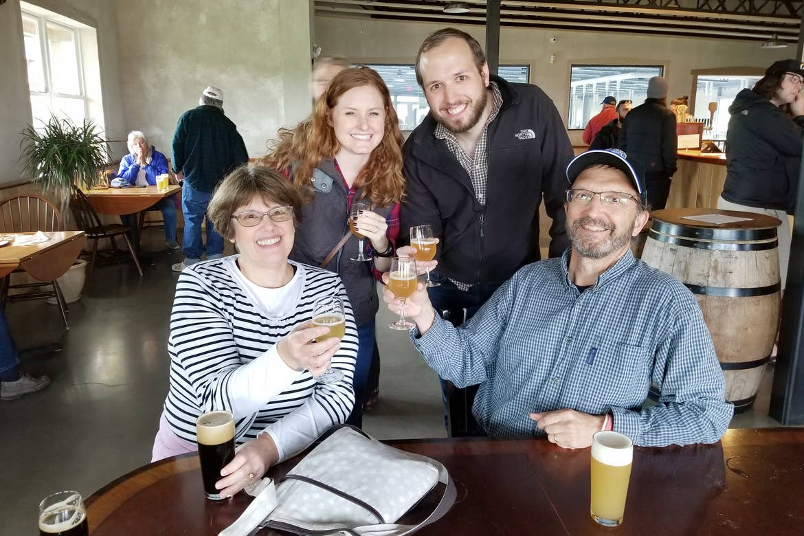 Two caucasian men (right) and two Caucasian women (left) hold up glasses of beer at Hill Farmstead Brewery in Vermont.