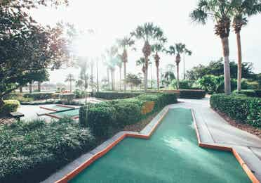 Outdoor mini golf course surrounded by palm trees in the West Village at Orange Lake Resort near Orlando, Florida