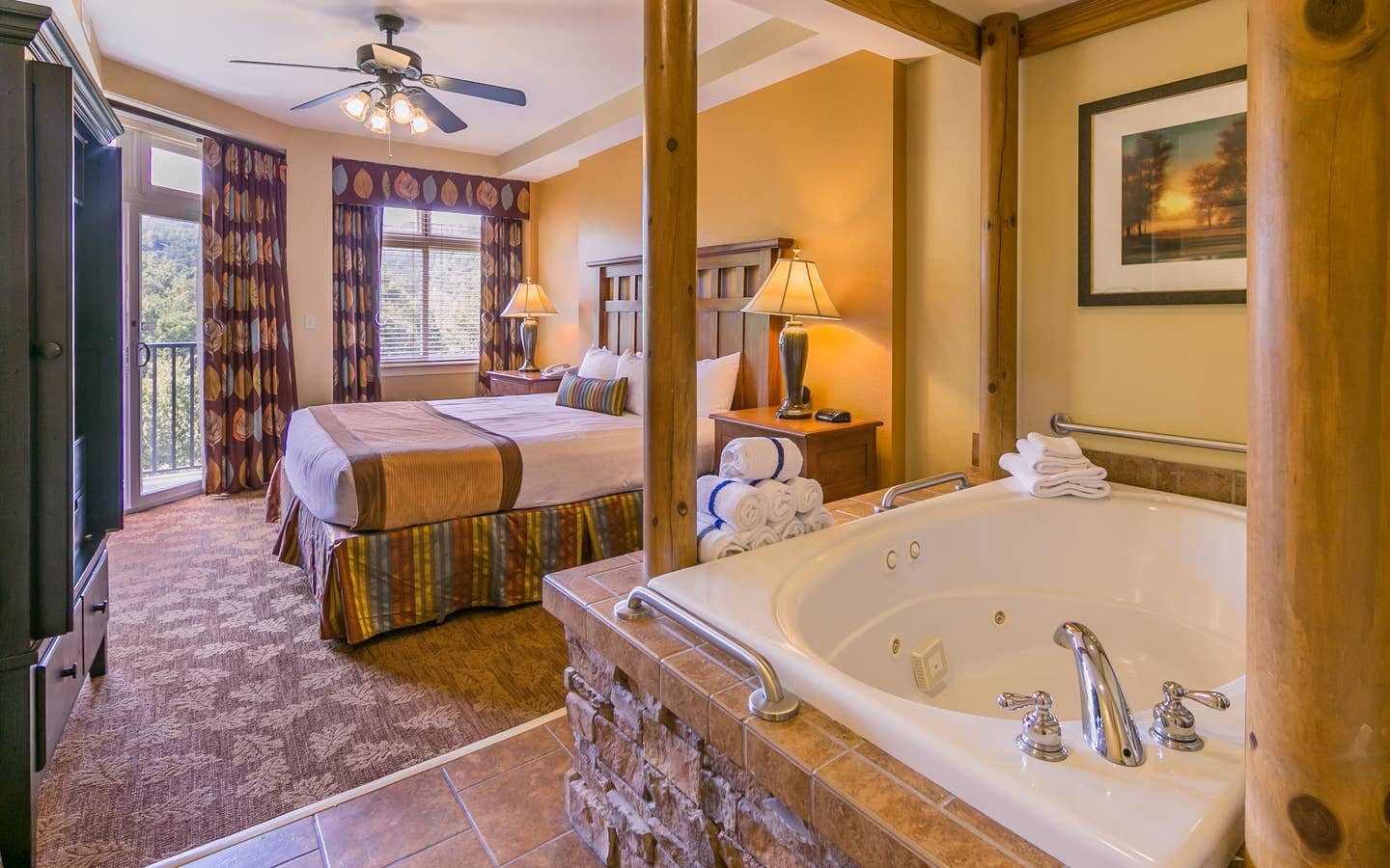 Bedroom with a bed and jacuzzi tub at Smoky Mountain Resort in Gatlinburg, Tennessee.