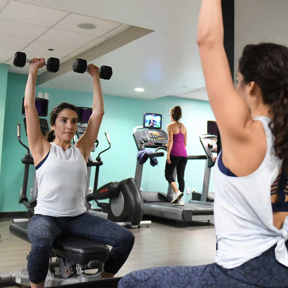 A woman lifting free weights at a fitness center in front of a mirror