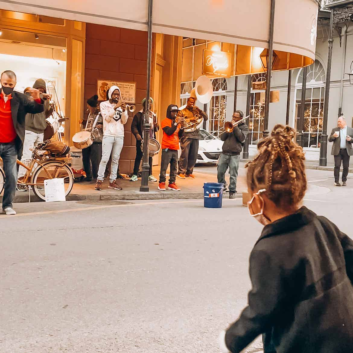 Featured Contributor, Sally Butan of @butanclan's daughter wears a mask and jacket while dancing to a live brass band on Bourbon St. in New Orleans, Louisiana.
