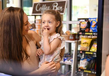 A woman holding her daughter in a store