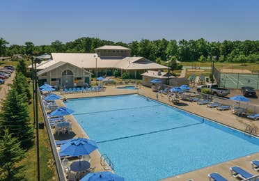 Outdoor pool with beach chairs and umbrellas at Fox River Resort in Sheridan, Illinois