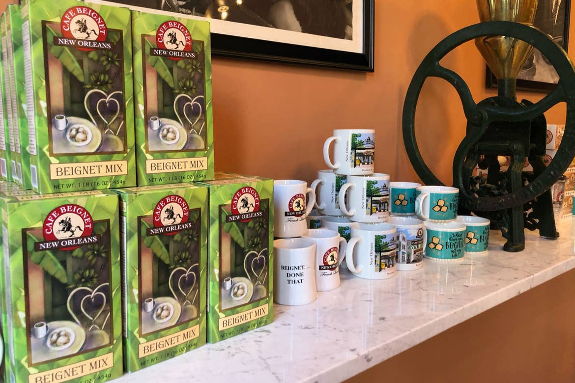 Multiple boxes of Cafe Beignet Mix on a countertop alongside branded mugs.