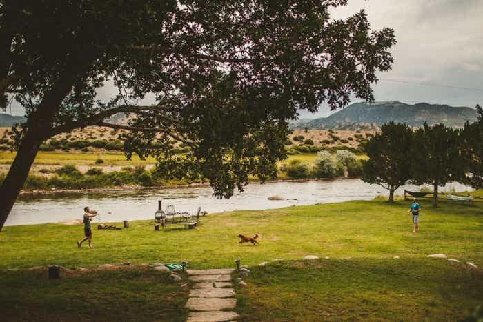 Two men throw a frisbee at each other while a dog runs in-between the two of them on a grassy area near a creek.