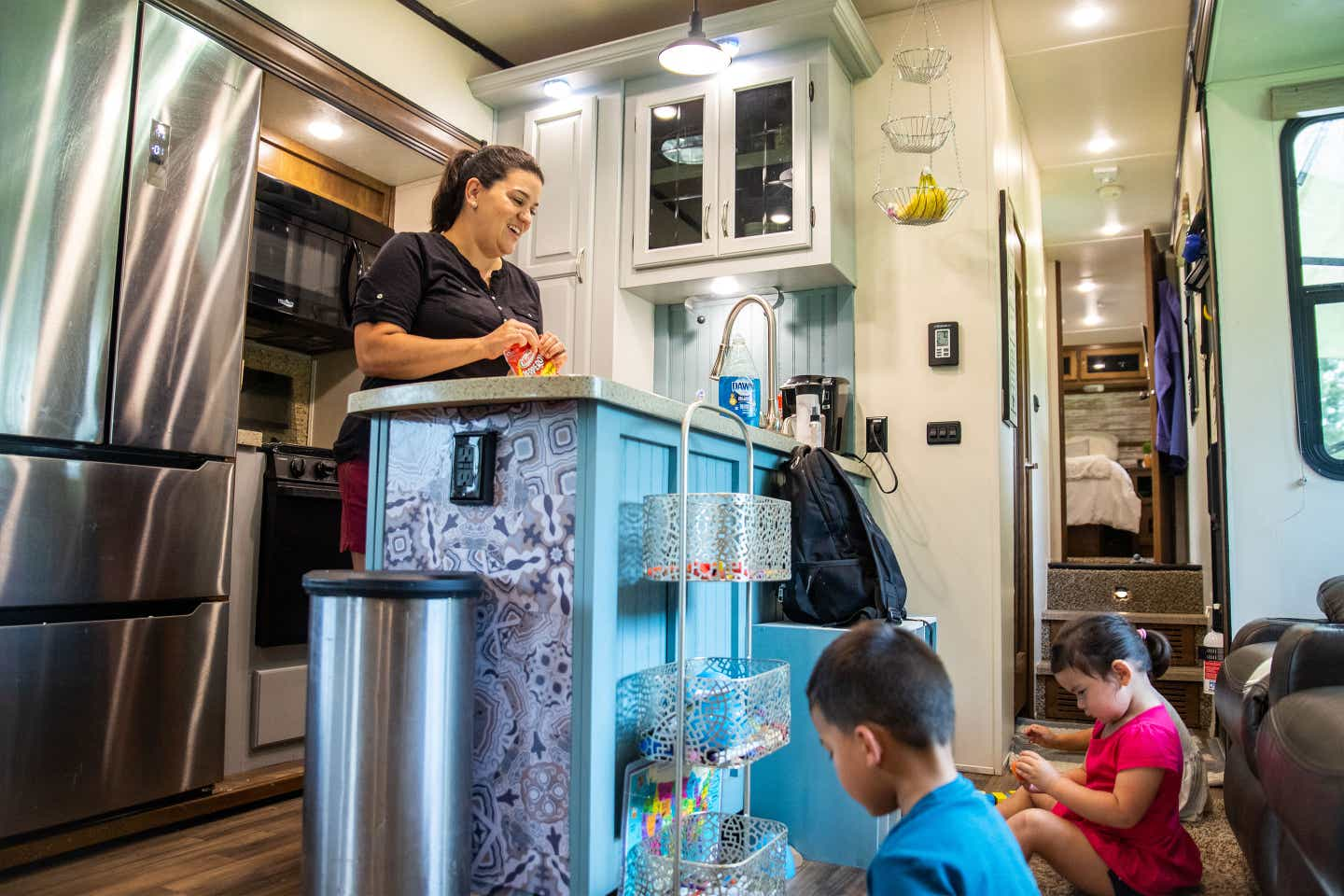 Angelica (left) preps in their RV kitchen while the children (bottom-right) play on the ground with their toys.