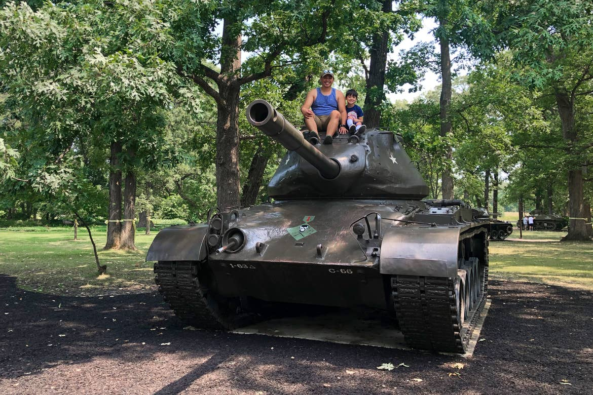 A man and child sit on the top of an old  US Army tank.