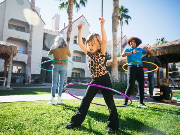 Two kids and a team member hula hooping at Desert Club Resort in Las Vegas, Nevada.