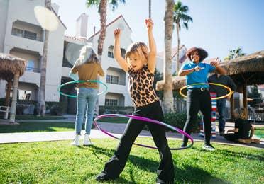 Two kids and a team member hula hooping at Desert Club Resort in Las Vegas, Nevada.