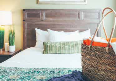 Bed with beach bag on covers in a villa in River Island at Orange Lake Resort near Orlando, Florida