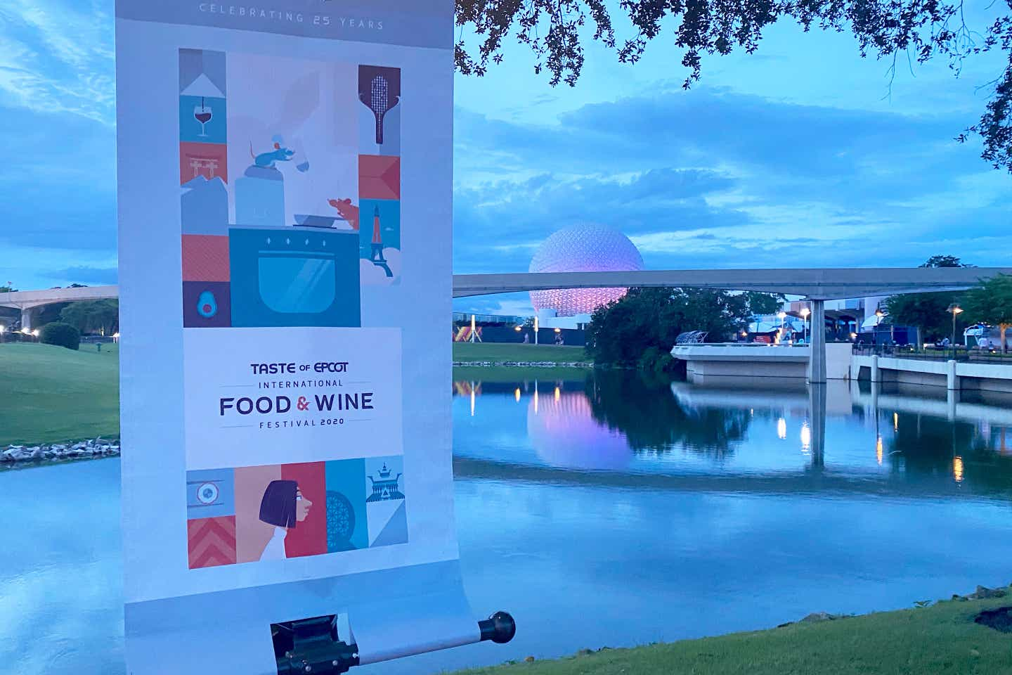 Taste of EPCOT International Food & Wine Festival banner stands on a post as Future World at EPCOT can be seen in the background.