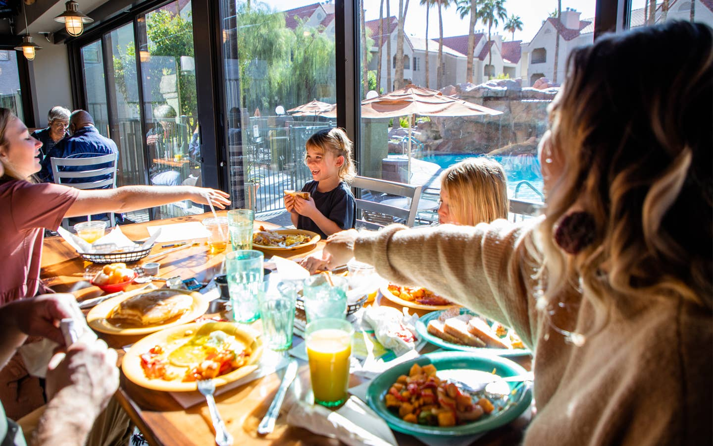 Family eating breakfast at Gold Mine Bar & Grill with pool view at Desert Club Resort in Las Vegas, Nevada.
