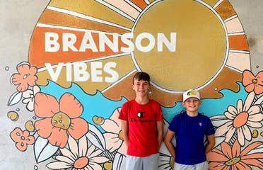 Two boys stand in front of a mural that reads,  'Branson Vibes'.