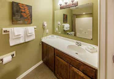 Bathroom with large counter area, sink, and mirror in a studio room at Piney Shores Resort in Conroe, Texas