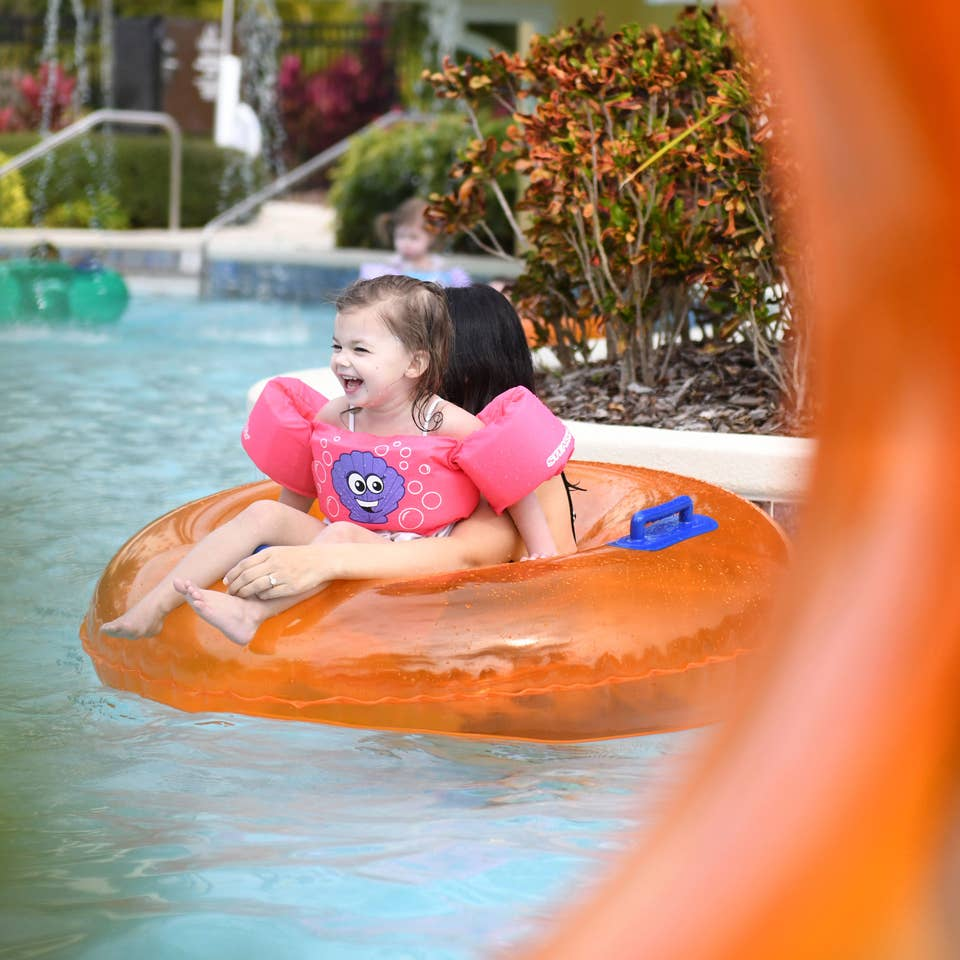 Young girl and mom floating down lazy river in inner tube at Orange Lake Resort near Orlando, Florida