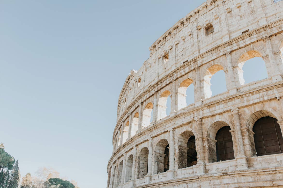 The white stone exterior of the Coliseum in Rome, Italy under a light blue sky.