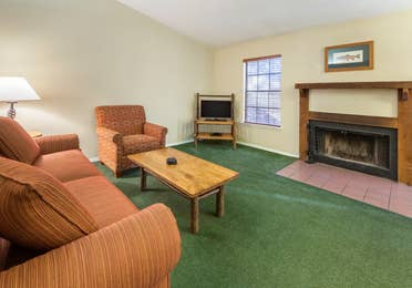 Living room with couch, accent chair, and fireplace in a two-bedroom cabin at Ozark Mountain Resort in Kimberling City, Missouri