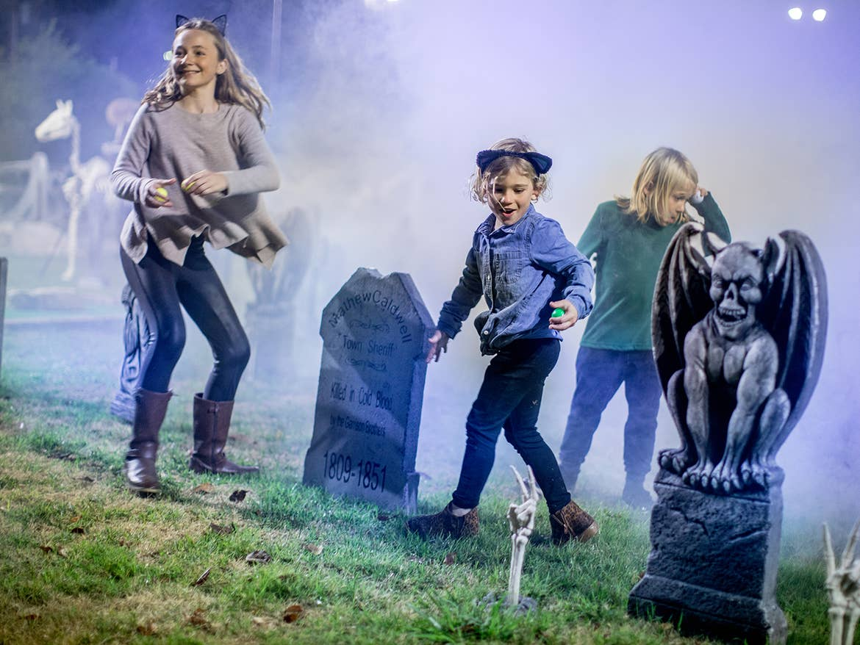 Children doing Halloween-themed scavenger hunt outdoors surrounded by fog.