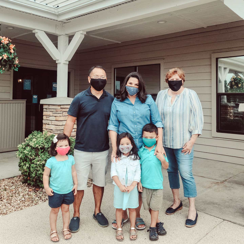 The Kajiwara family wearing masks outside of the Holiday Hills Resort.