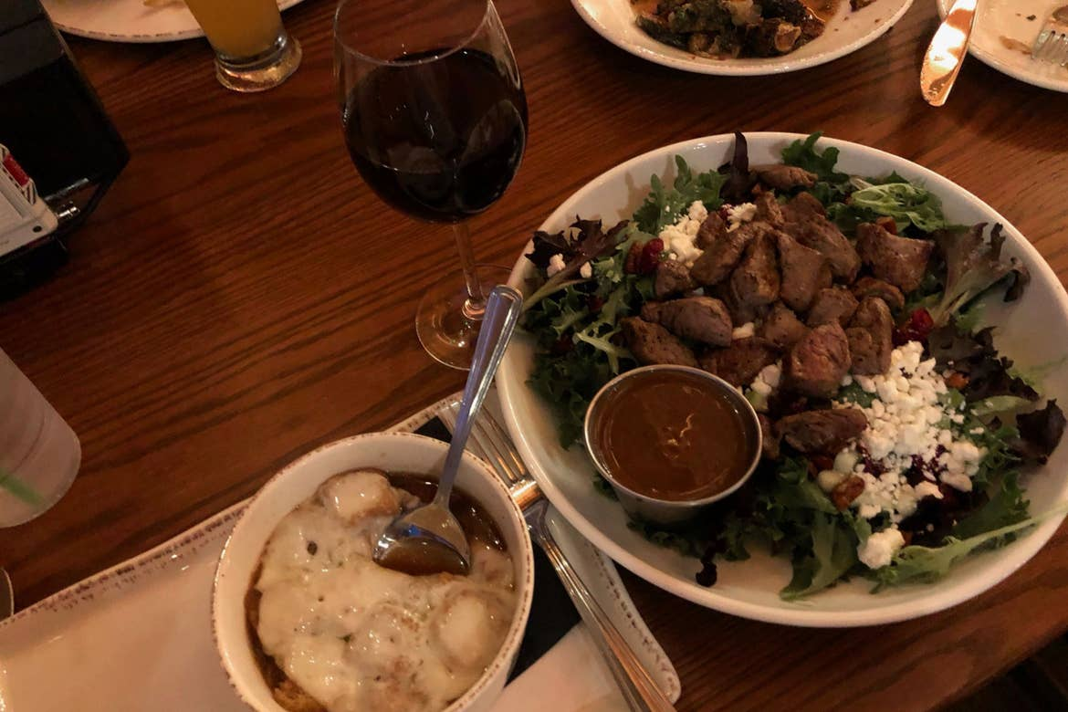 French Onion Soup (left), a glass of red wine (middle) and salad filled with greens, apples, caramelized pecans, cranberries and cheese on a wood table.