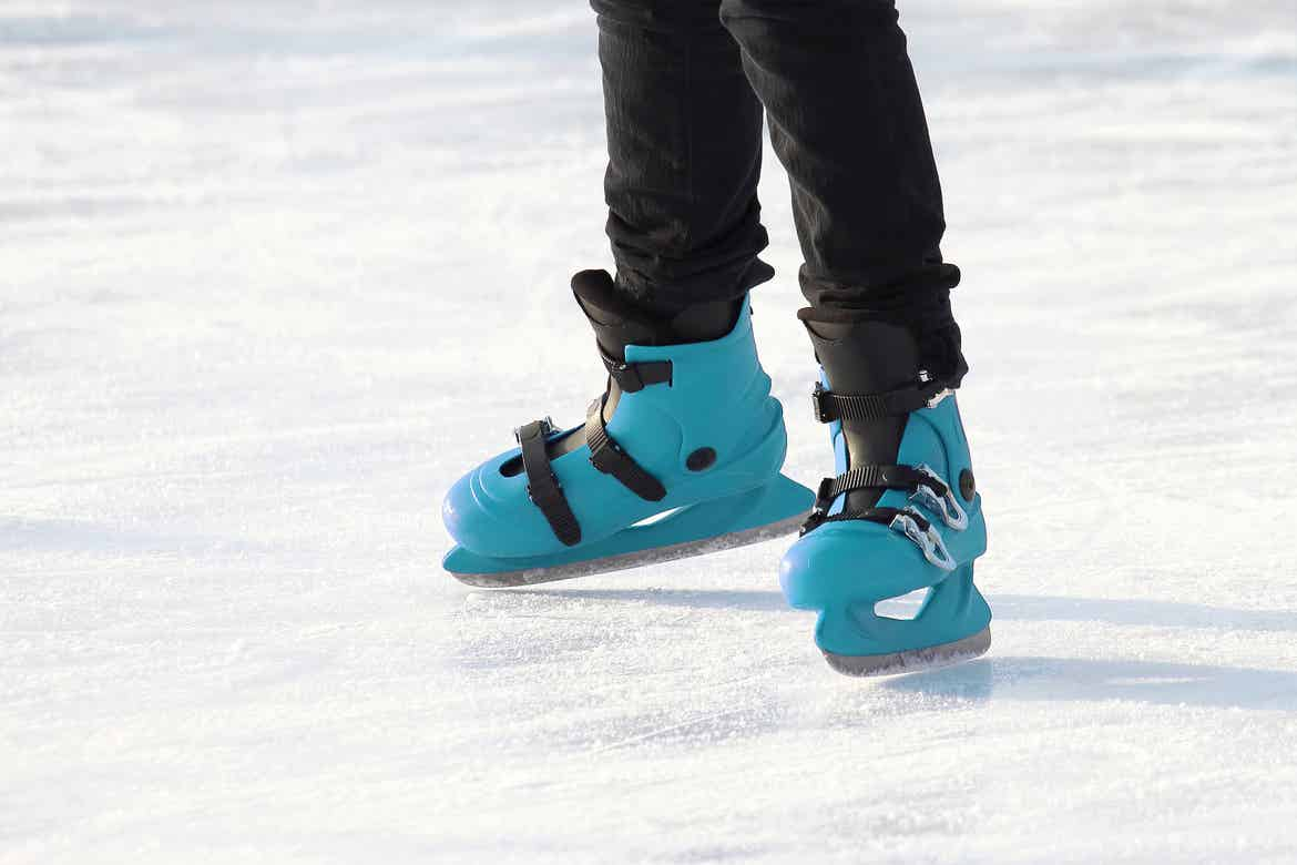 A child skates on ice wearing a black snow pants and a pair of blue ice skates.