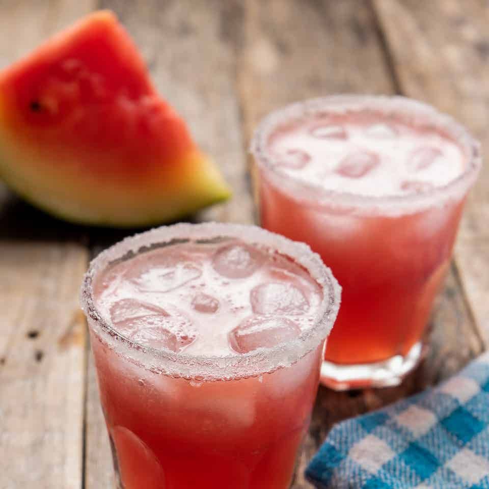 Two glasses of Melon Margaritas sit on a wooden plank table in front of a watermelon wedge.