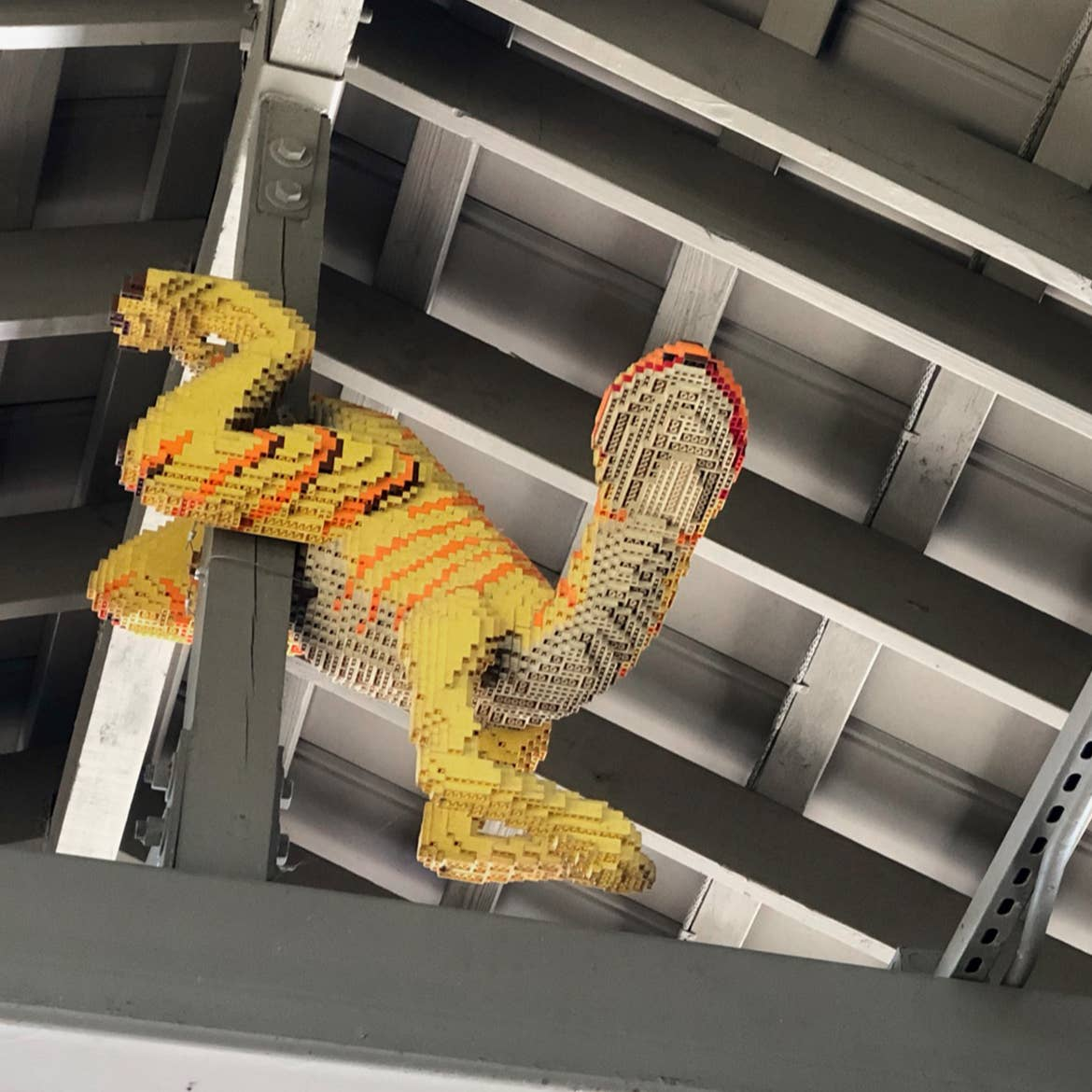 A dinosaur figurine made of LEGOS hangs on a structural beam.