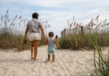Adult and child walking onto beach at Cape Canaveral Beach Resort.