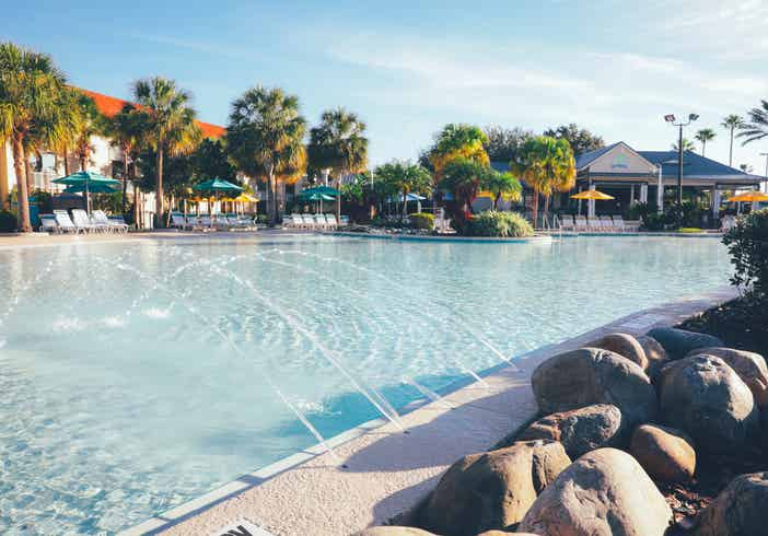 Pool with beach chairs and palm trees and Breezes Restaurant & Bar in West Village at Orange Lake Resort near Orlando, Florida