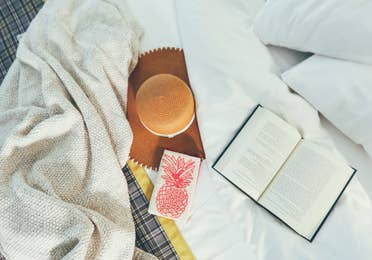 Closeup of book, throw blanket, and sun hat on top of bed in a villa in River Island at Orange Lake Resort near Orlando, Florida