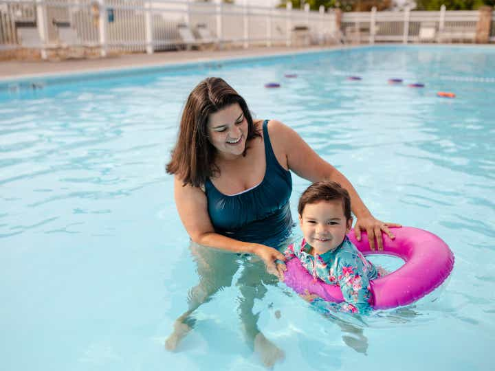 Adult helping child float in outdoor pool at Holiday Hills Resort in Branson, Missouri.
