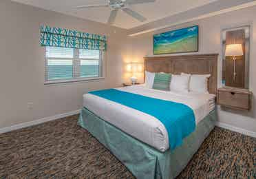 Bedroom with window with view of ocean and coastal decor in a two-bedroom villa at Panama City Beach Resort