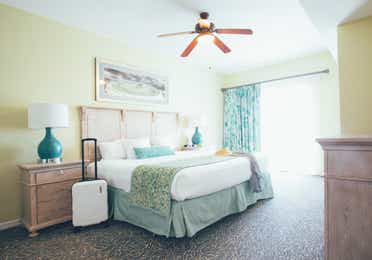 Bedroom with access to balcony and luggage in a villa in River Island at Orange Lake Resort near Orlando, Florida