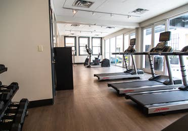 Fitness center with treadmills, free weights and stationary bicycle at New Orleans Resort in Louisiana.