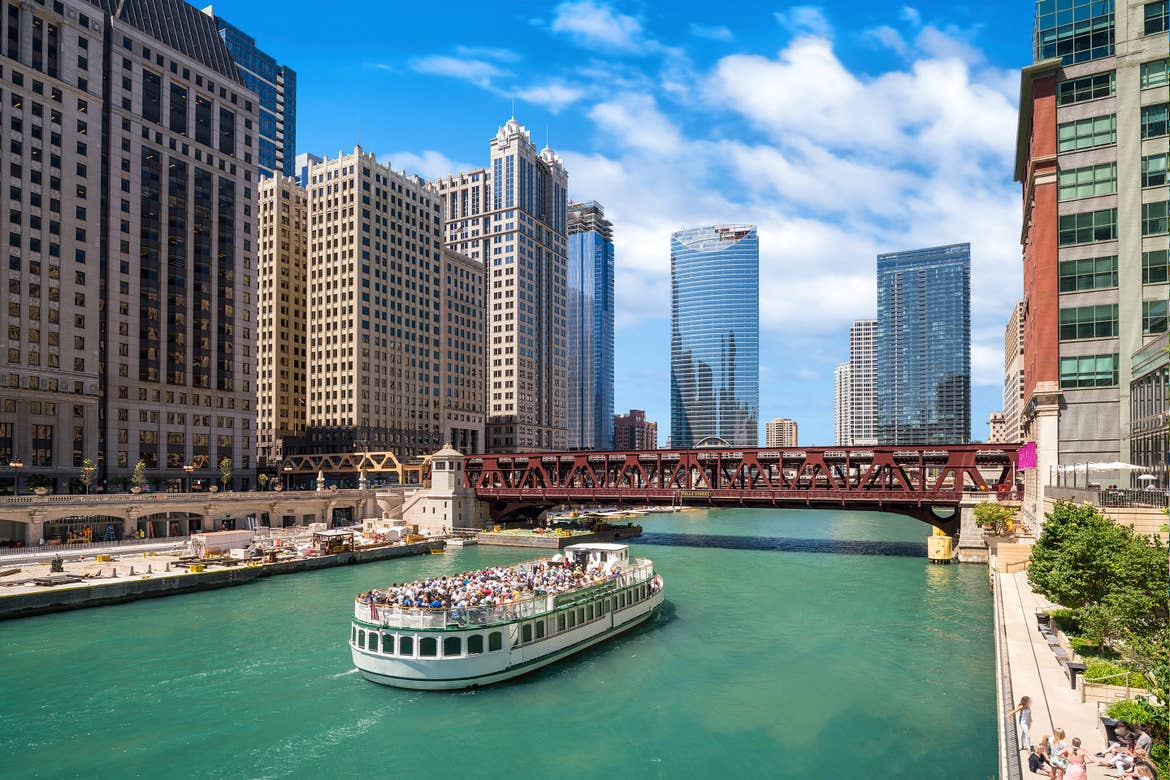 A tour boat makes its way down the Chicago River under iconic bridges and skyscrapers.
